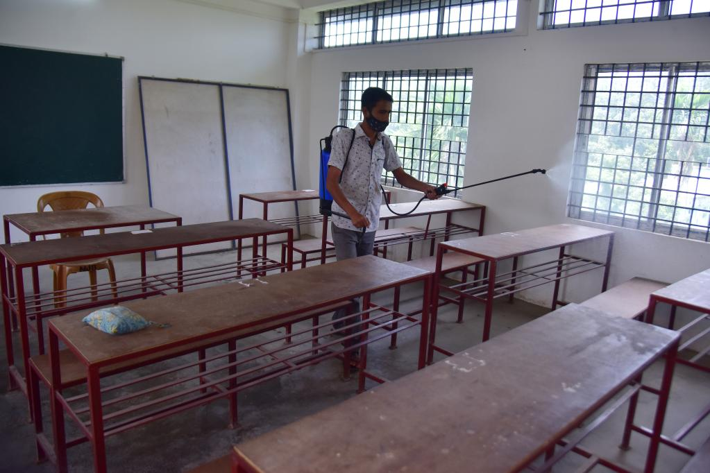 Worker disinfects classroom at school to prepare for reopening in Nagaon district, India